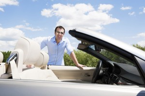 Smiling man and a cabriolet car against blue sky.
